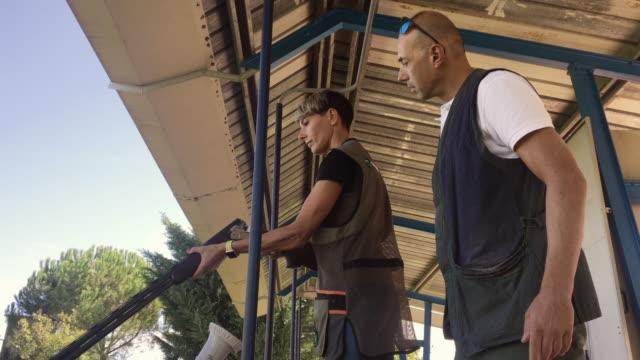 stockvideo's en b-roll-footage met volwassen man onderwijs volwassen vrouw hoe te laden en schieten een shotgun op shooting range - jachtgeweer