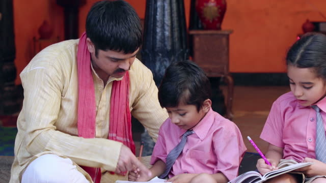 adult man teaching his children in the home, delhi, india - genderblend stock videos & royalty-free footage