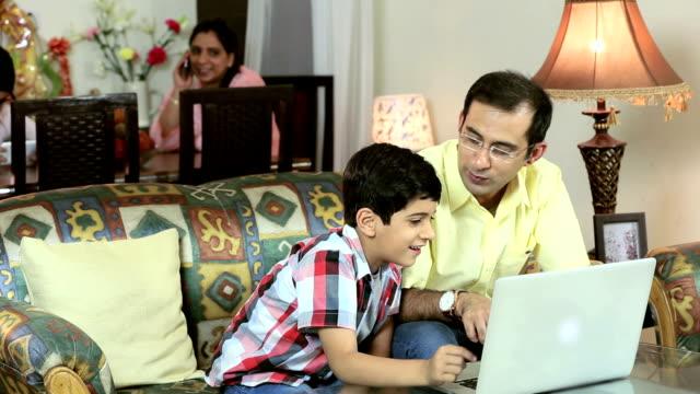 Adult man teaching laptop to his son, Delhi, India