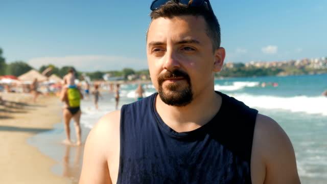ビーチの上を歩くと、電話で話している大人の男 - ゴーティー点の映像素材/bロール