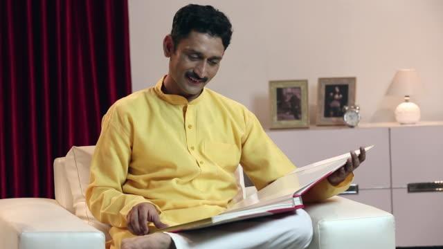 stockvideo's en b-roll-footage met adult man watching picture album, delhi, india - driekwartlengte