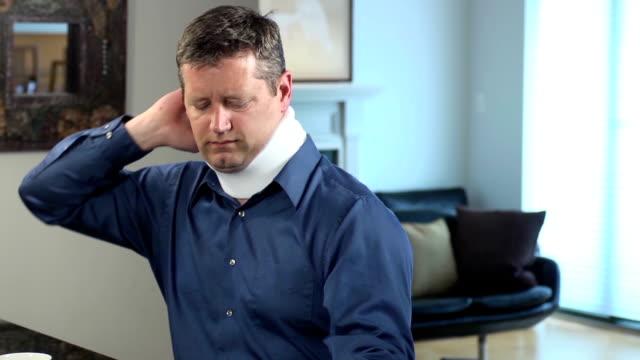 erwachsener mann trägt halsmanschette bringt beschwerden - unfall ereignis mit verkehrsmittel stock-videos und b-roll-filmmaterial