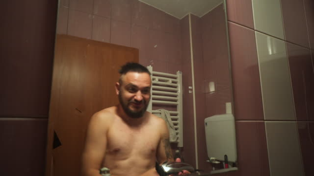 vídeos de stock, filmes e b-roll de o homem adulto com uma barba corta seu cabelo no banheiro - barba