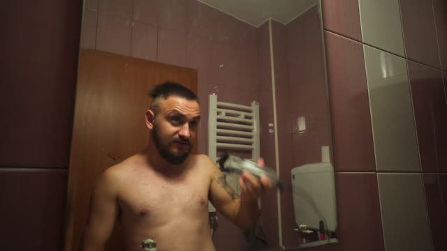 adult man with a beard cuts his hair in bathroom - raso video stock e b–roll