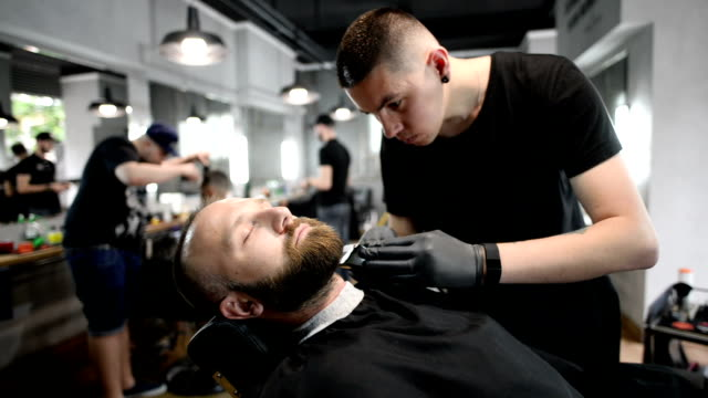 adult man with beard in a barber shop - barber shop stock videos & royalty-free footage