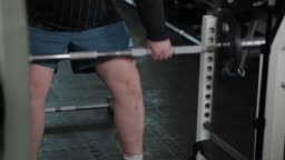 Adult man with overweight performs deadlift in the gym