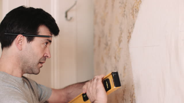 adult man with spirit level measuring wall in new home - one mid adult man only stock videos & royalty-free footage