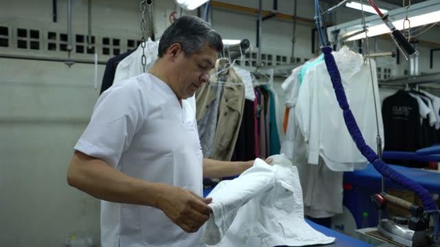 ランドリーサービスで働く大人の男性アイロンシャツ笑顔 - コインランドリー点の映像素材/bロール