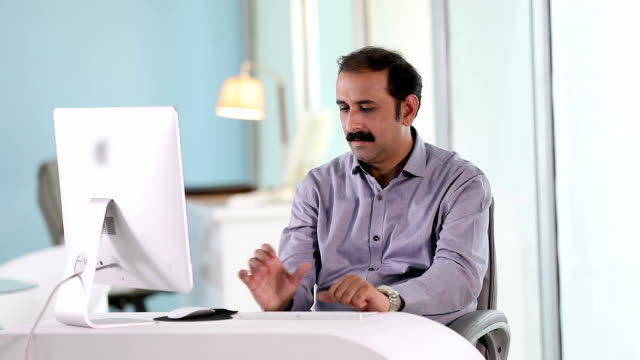 Adult man working on desktop PC at office, Delhi, India