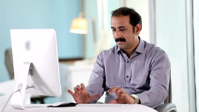 Adult man working on desktop PC at office, Delhi, India