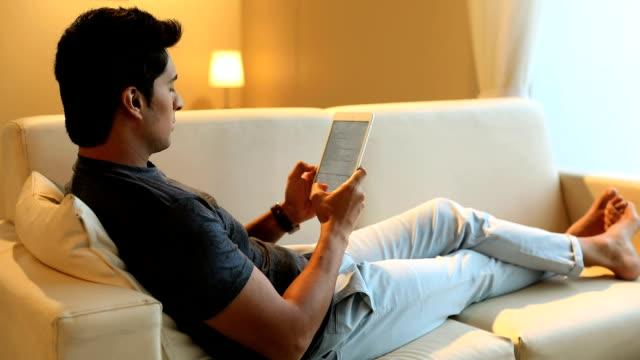 stockvideo's en b-roll-footage met adult man working on digital tablet, delhi, india - achterover leunen