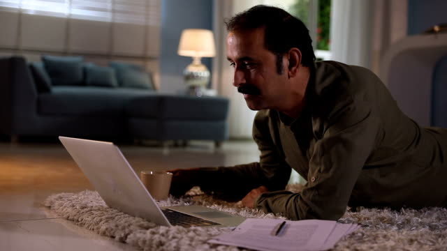 adult man working on laptop at home, delhi, india - rechnung stock-videos und b-roll-filmmaterial