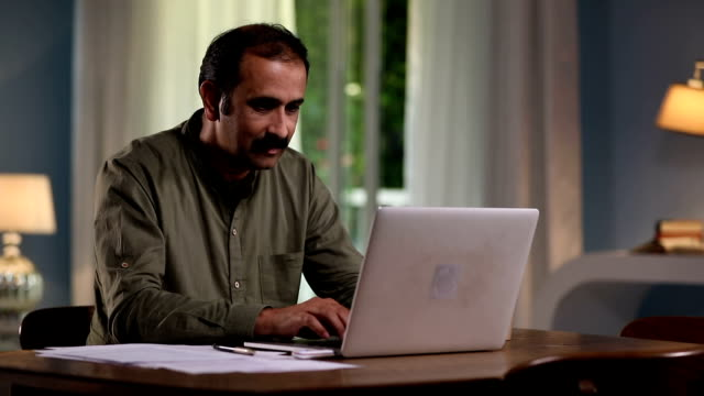 Adult man working on laptop at home, Delhi, India