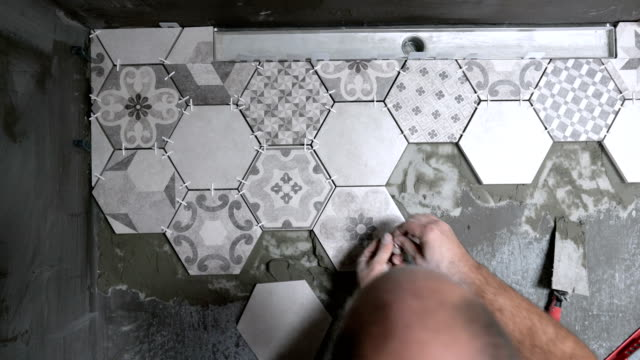 adult mason installing tiles on the bathroom floor - tile stock videos & royalty-free footage
