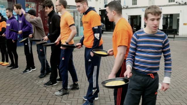 vidéos et rushes de adult men take place annual shrove tuesday pancake race in fore street on on february 28, 2017 in trowbridge, england. - mardi gras fête religieuse