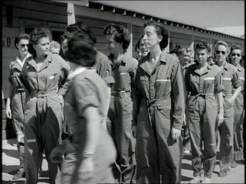 vidéos et rushes de adult middle-aged caucasian woman looking at wristwatch, whistling. adult female recruits wearing jumpsuits, running out of barracks, lining up.... - pilote