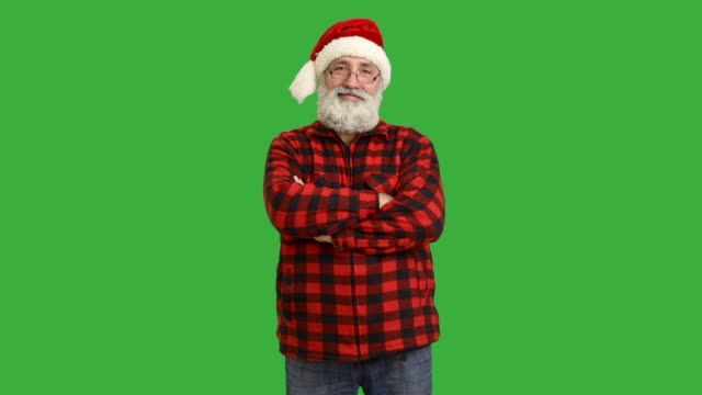 adult senior beard man crosses his arms in a hat santa claus  on a green background - santa hat stock videos & royalty-free footage