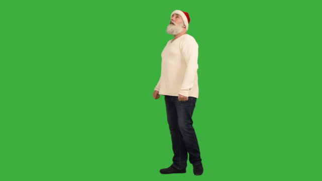 adult senior beard man  it looks and wrapped around himself in a hat santa claus  on a green background - santa hat stock videos & royalty-free footage