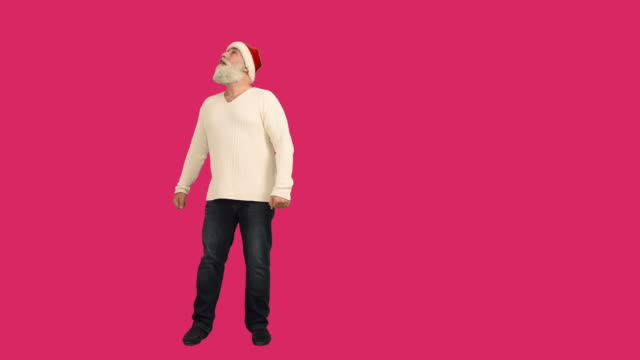 adult senior beard man  it looks and wrapped around himself in a hat santa claus  on a crimson background - santa hat stock videos & royalty-free footage