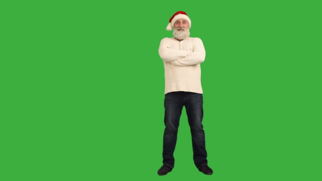 adult senior beard man  looking at the camera smiling and  crosses his arms in a hat santa claus  on a green background - santa hat stock videos & royalty-free footage