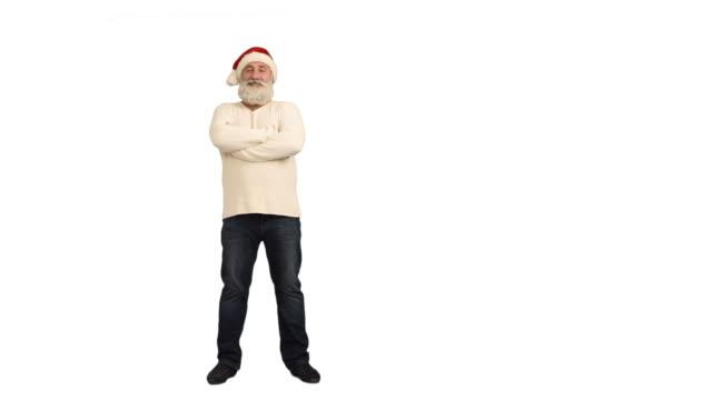 vídeos de stock e filmes b-roll de adultos idosos barba, a olhar para a câmara sorridente e atravessa os seus braços em um chapéu de santa natal em um fundo branco - chapéu do pai natal