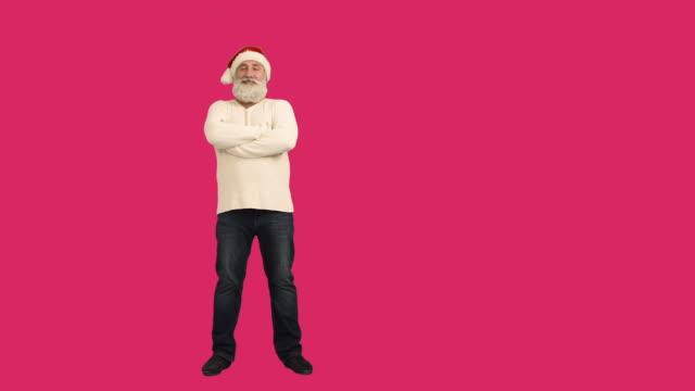 vídeos de stock e filmes b-roll de senior adulto barba, a olhar para a câmara sorridente e atravessa os seus braços em um chapéu de santa natal em um fundo de garganta - chapéu do pai natal
