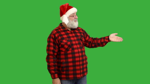 adult senior beard man showing an copy space and  crosses his arms in a hat santa claus  on a green background - santa hat stock videos & royalty-free footage