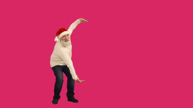 vídeos de stock e filmes b-roll de senior adulto barba homem mostrando uma espaço de cópia e atravessa os seus braços em um chapéu de santa natal em um fundo de garganta - chapéu do pai natal