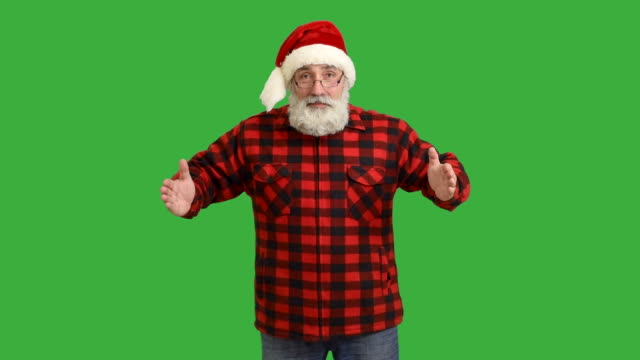 adult senior beard man showing an copy space and showing a thumb  in a hat santa claus  on a green background - santa hat stock videos & royalty-free footage