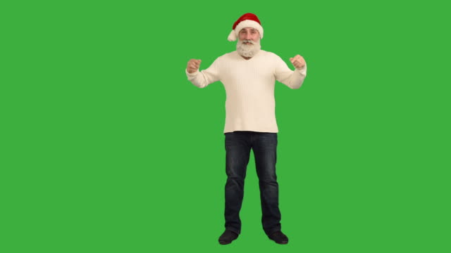 adult senior beard man showing an copy space  and shows the thumbs up in a hat santa claus  on a green background - santa hat stock videos & royalty-free footage