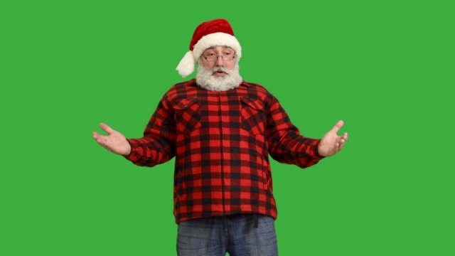 adult senior beard man showing an copy space in a hat santa claus  on a green background - santa hat stock videos & royalty-free footage