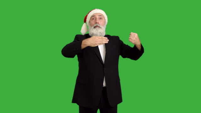 adult senior beard man shows a wonderful focus  in a hat santa claus  on a green background - santa hat stock videos & royalty-free footage