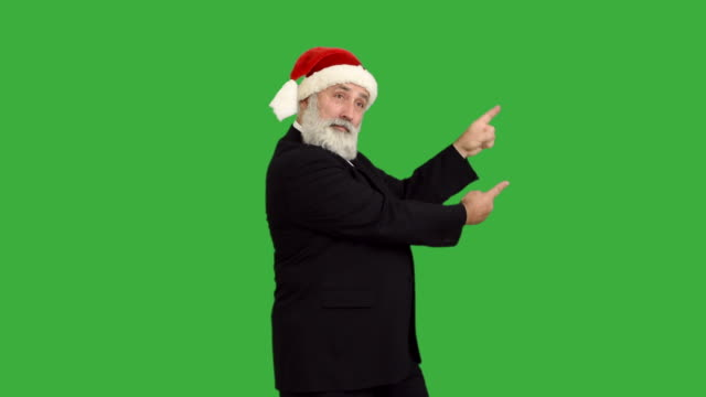 adult senior beard man shows copy space  in a hat santa claus  on a green background - santa hat stock videos & royalty-free footage