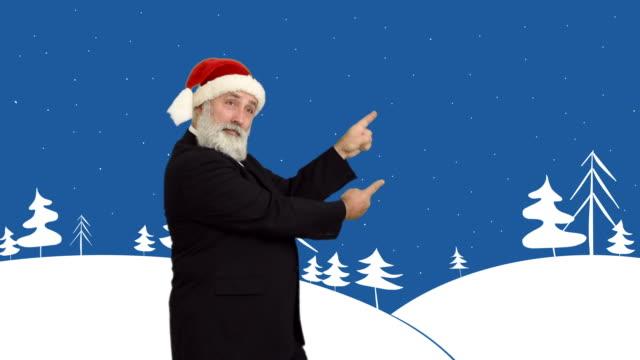 vídeos de stock e filmes b-roll de senior adulto barba homem mostra cópia espaço em um chapéu de santa natal em um fogo de fundo do tema do inverno - chapéu do pai natal