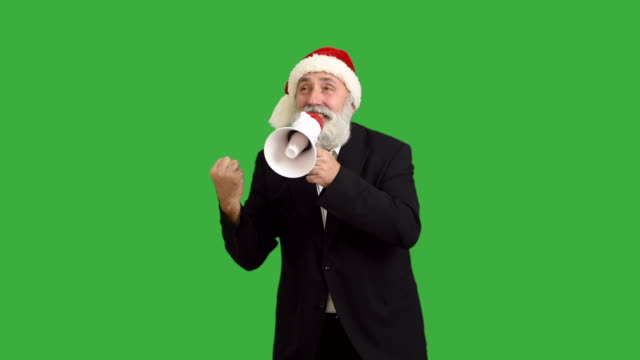 adult senior beard man shows copy space  in a hat santa claus with a megaphone  on a green background - santa hat stock videos & royalty-free footage