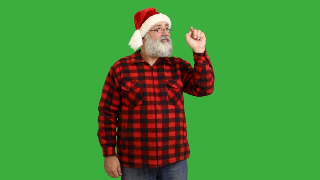 adult senior beard man wrote 2016 and crosses his arms in a hat santa claus  on a green background - santa hat stock videos & royalty-free footage
