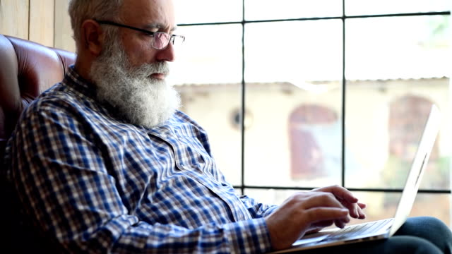 Adult senior bearded man sitting with a laptop