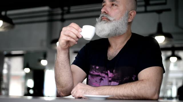 adult senior  brutal man drinks coffee