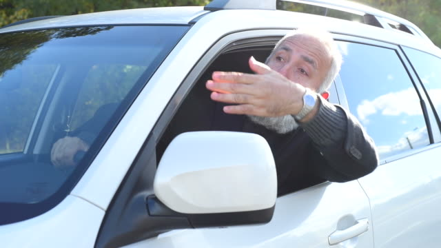 adult senior businessman arguing with someone from the car