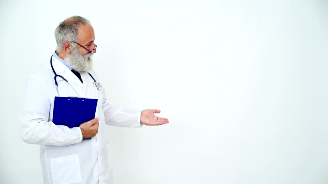 adult senior doctor showing copy space and smiling on a gray background - shirt and tie stock videos & royalty-free footage