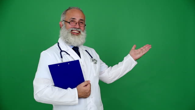 adult senior doctor showing copy space and smiling on a green background
