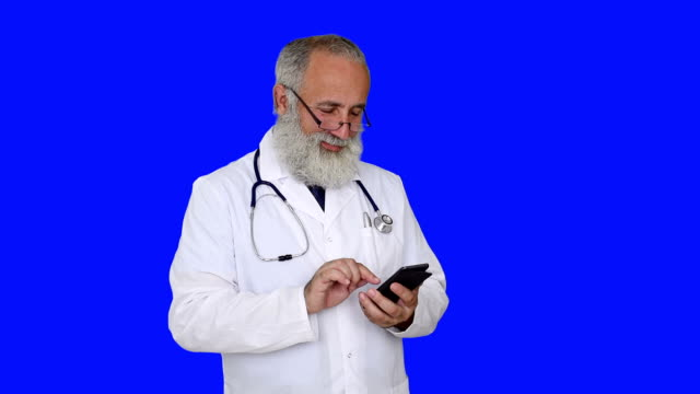 adult senior doctor smiling and uses a smartphone on a blue background - shirt and tie stock videos & royalty-free footage