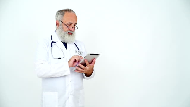 Adult senior doctor smiling and using a tablet on a grey background