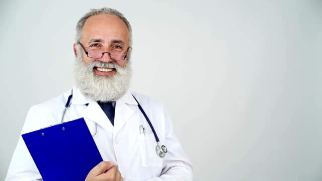 adult senior doctor smiling looking at the camera on a grey background
