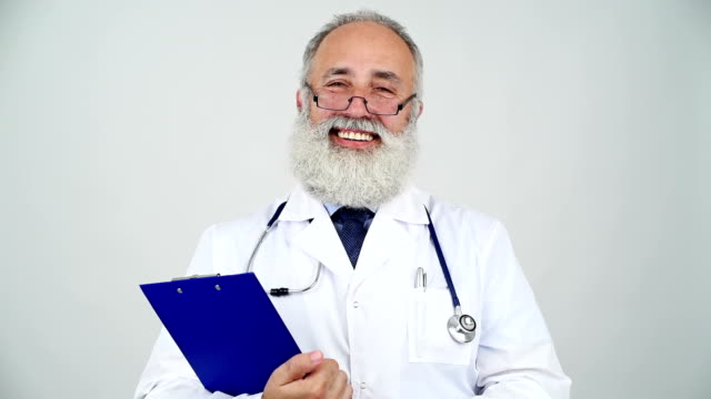 adult senior doctor smiling looking at the camera on a grey background - grey eyes stock videos & royalty-free footage