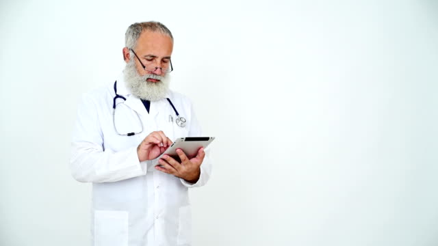 adult senior doctor  uses a tablet on a grey background