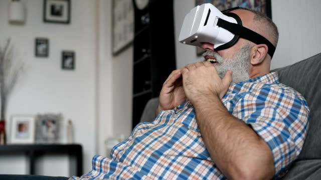 adult senior man and a virtual reality headset. graybearded man using vr glasses - x rated stock videos and b-roll footage