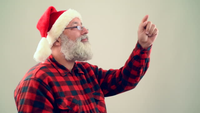 adult senior man draws in air numbers of the new year in the santa claus hat on a gray background - santa hat stock videos & royalty-free footage