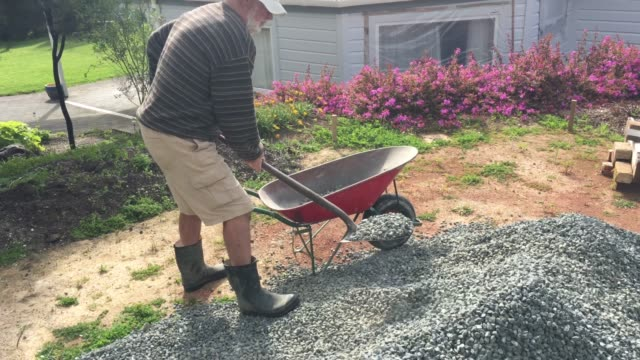 adult senior man filling a wheel barrel with gravel - wheelbarrow stock videos and b-roll footage