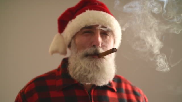 adult senior man in santa hat smoking a cigar on a gray background. - santa hat stock videos & royalty-free footage